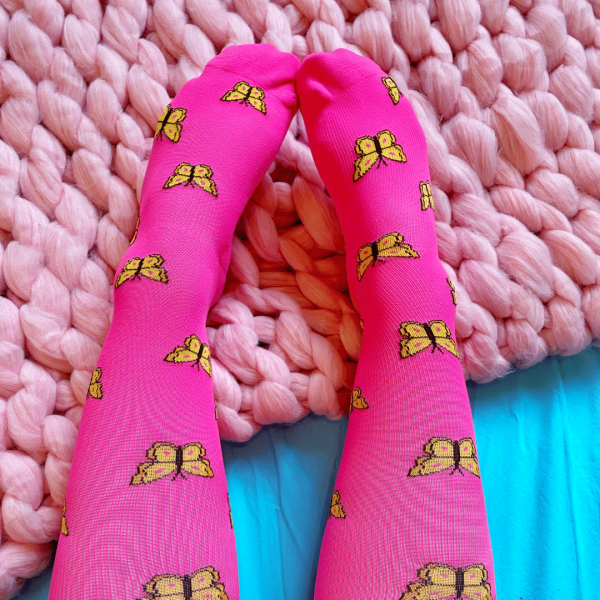 Bright magenta compression socks with yellow butterlies. The background is a pink knitted blanket with a blue sheet.