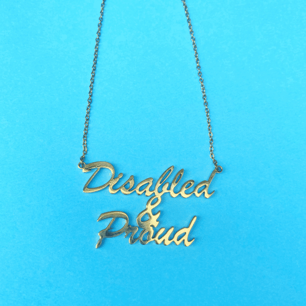 A gold necklace on a blue background. In script lettering it says, 'Disabled & Proud'