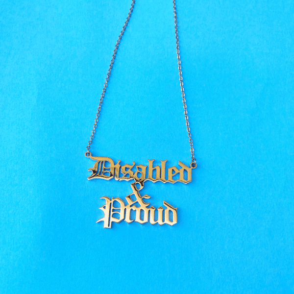 A gold necklace on a blue background. In gothic lettering it says, 'Disabled & Proud'