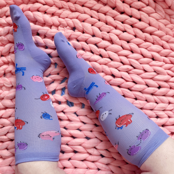 Purple compression socks with little blue, pink and red organs on them.