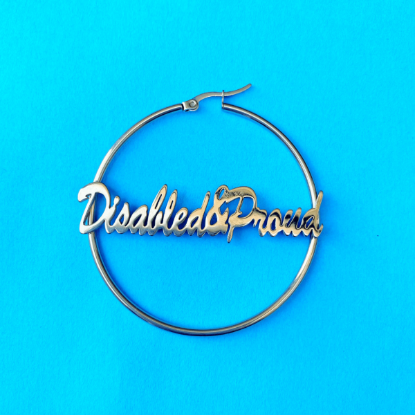 Close up of a single disabled and proud script lettering earring