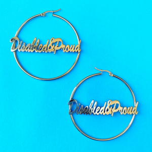 Close up of the two gold script lettering disabled and proud hoop earrings
