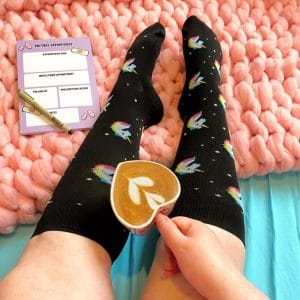 Feet wearing black compression socks with cute unicorn pattern. There is a pink knitted blanket beneath them, a hand is holding a coffee with a cute heart detail and there is a pen and pad on the blanket