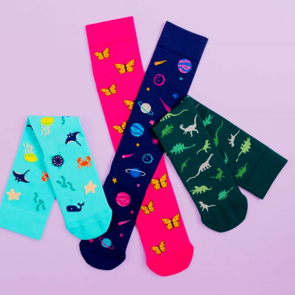 Compression socks all piled in a bunch, the designs are sea creatures, space, butterflies and dinosaur.
