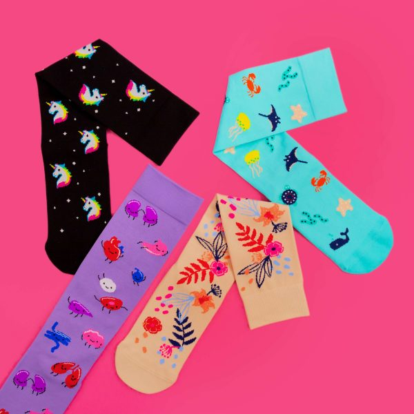 Several compression socks on a pink background. From left to right, unicorn, organs, floral and sea creatures are all present