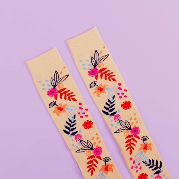 Light pink, floral socks with dark pink, blue and navy design on a purple background